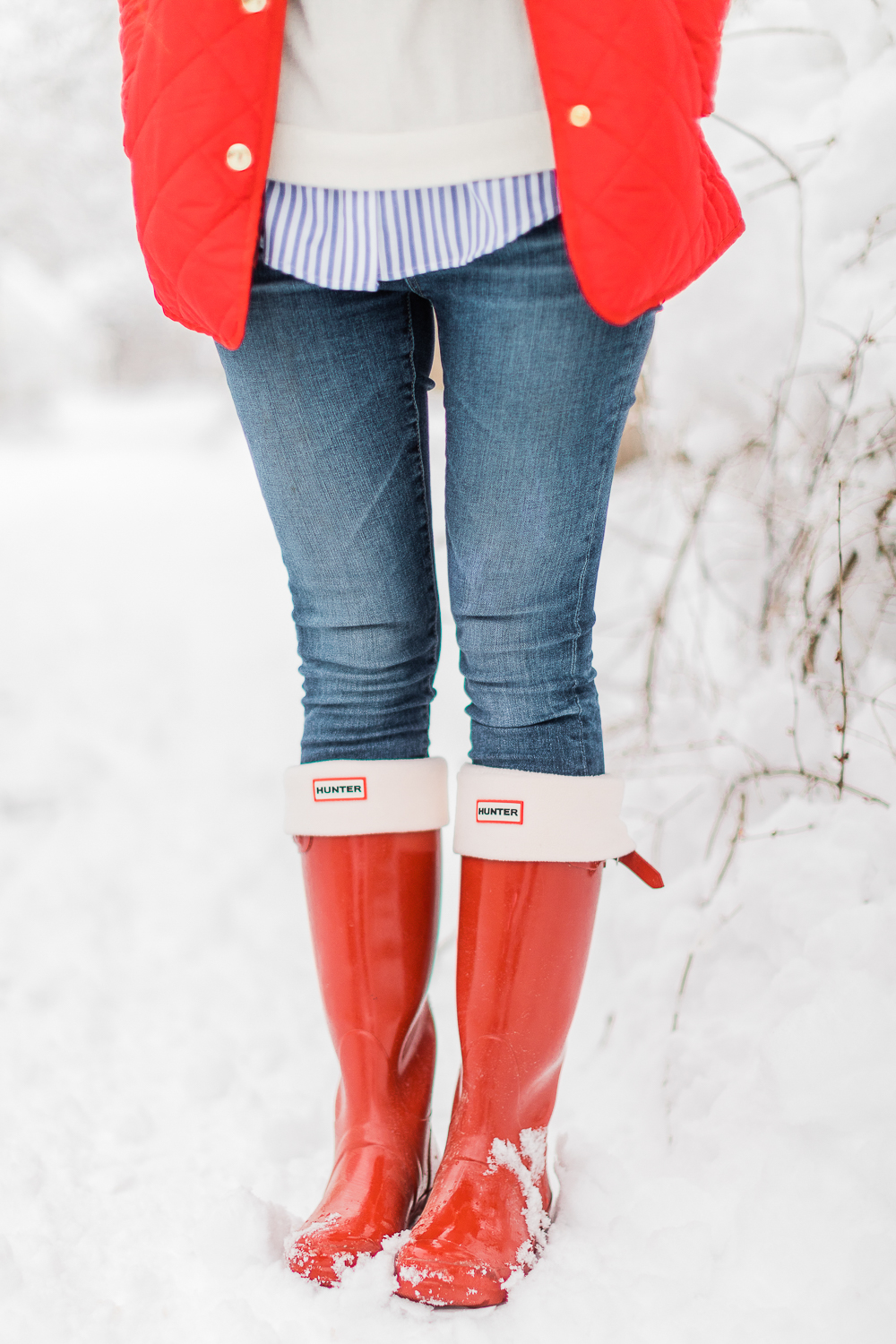 Preppy Winter Outfit: Red Quilted Jacket with Matching Red Hunter Boots by affordable fashion blogger Stephanie Ziajka from Diary of a Debutante, how to style red Hunter boots with tall welly boot socks, how to style a red quilted jacket, red quilted jacket styled with red tall Hunter boots, Hunter tall welly boot socks, a blue striped oxford, white crewneck sweater, and skinny jeans