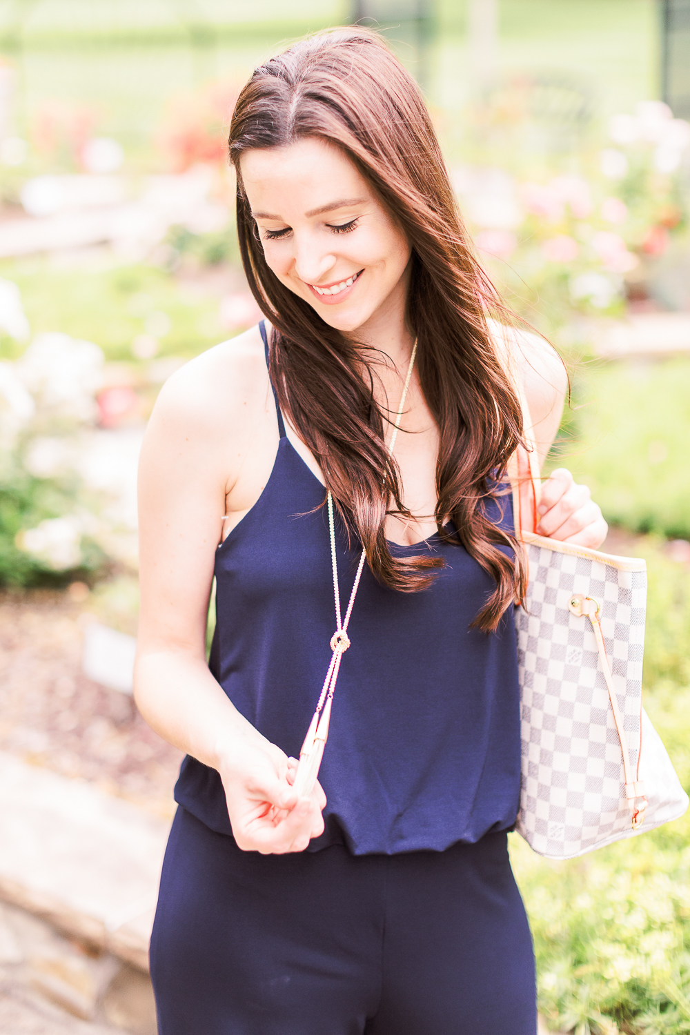 Summer Style Guide: How to Wear a Jumpsuit Casually by popular affordable fashion blogger Stephanie Ziajka from Diary of a Debutante, how to style navy jumpsuit, best shoes to wear with a jumpsuit, navy URBAN K Women's Racerback Jumpsuit, Louis Vuitton Neverfull Dupe Bag, Kendra Scott Phara Necklace