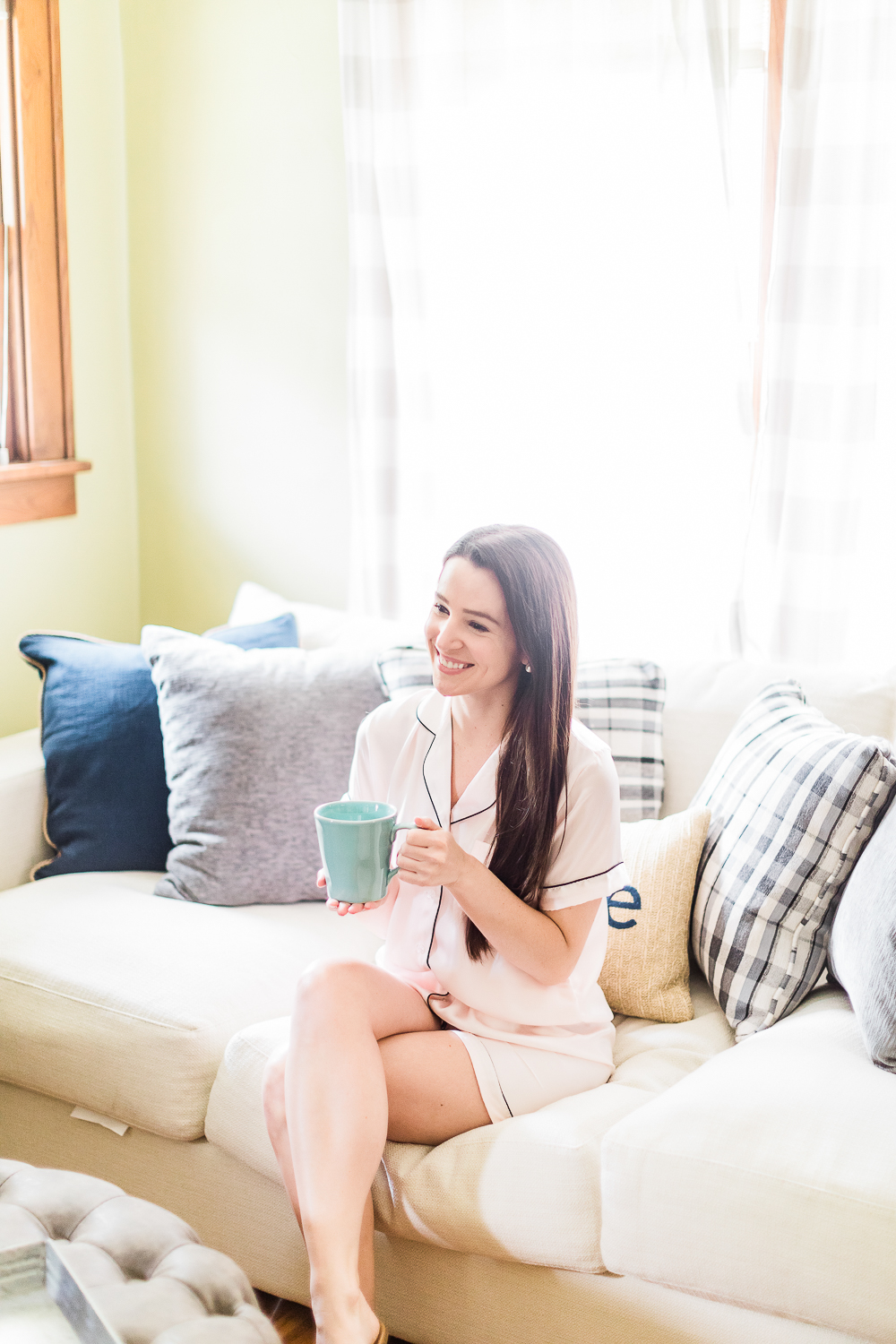 Morning Self-Care Routine by popular southern lifestyle blogger Stephanie Ziajka from Diary of a Debutante, drinking coffee on the couch, pink silk pajama set