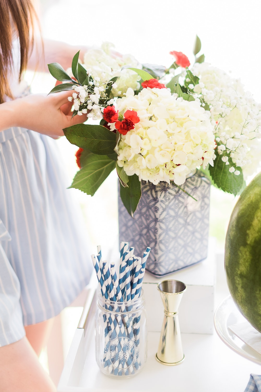 4th of July flower arrangement made using white hydrangeas, red carnations, baby's breath, greenery, and a blue and white ginger jar as a vase