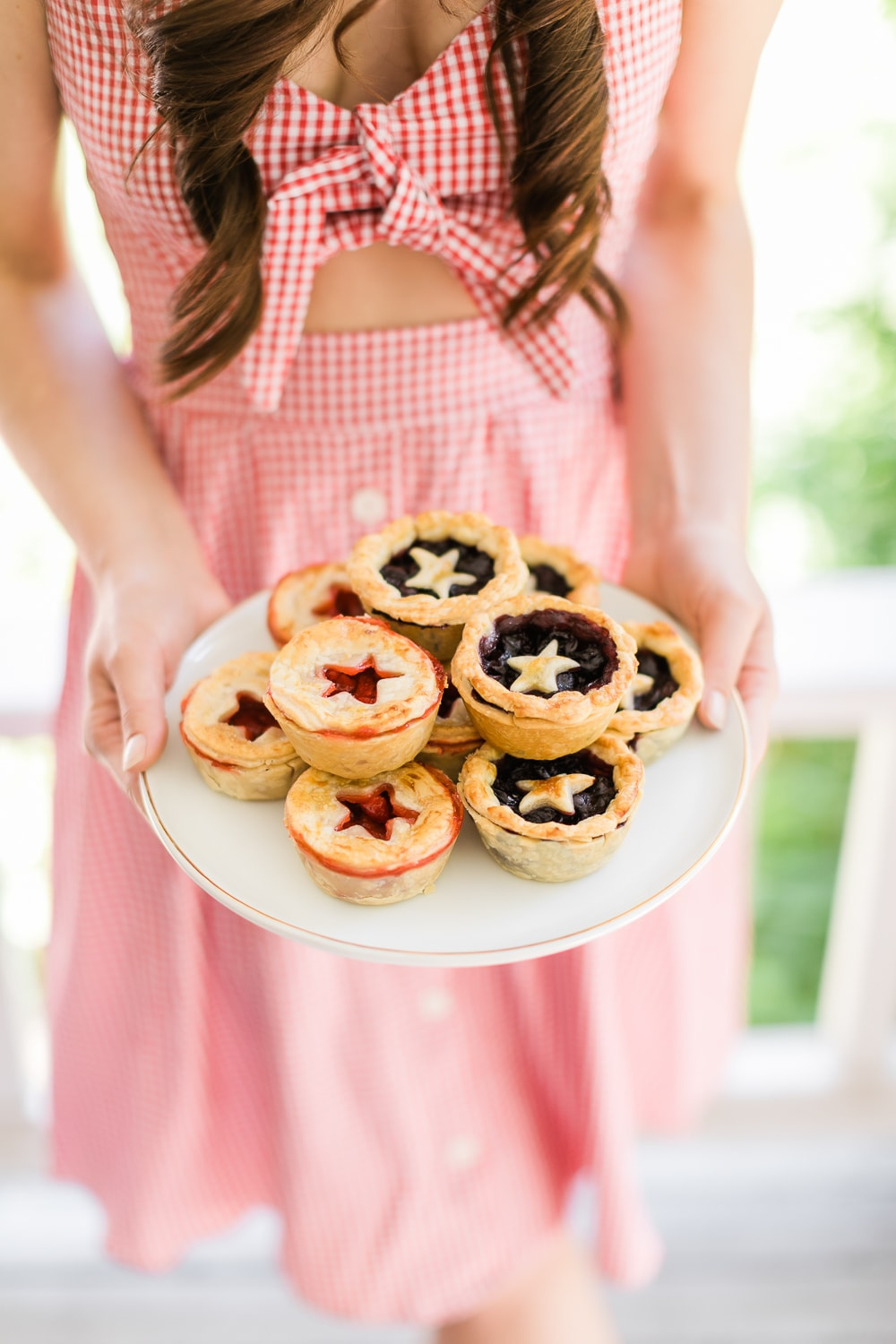 Affordable fashion blogger Stephanie Ziajka holding mini strawberry and blueberry pies in a red gingham dress on Diary of a Debutante